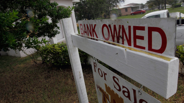"A ""bank owned"" sign in front of a home in Miami last October. (Getty Images)"