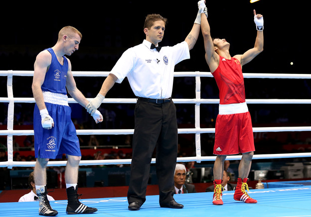 Shiming Zou of China is declared the winner over Paddy Barnes of Ireland during their men's light flyweight boxing semifinal in London. The match was scored a 15-15 tie; Zou won on the number of punches landed.