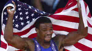 Jordan Burroughs celebrates with the U.S. flag after defeating Iran's Sadegh Saeed Goudarzi in the men's 74kg freestyle gold medal match.