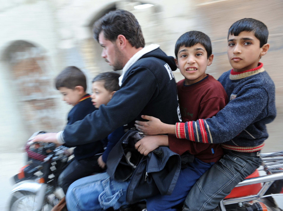 In northwestern Syria earlier this year, this man and boys fled fighting.