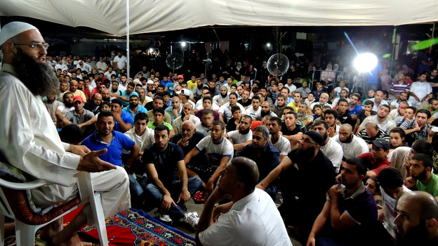 Sheik Ahmad Assir speaks to supporters at a tent encampment set up in protest against Hezbollah in Sidon, Lebanon. He accuses the Islamist militant group of using resistance against Israel as a smokescreen for another aim: advancing Iranian regional hegemony. (NPR)