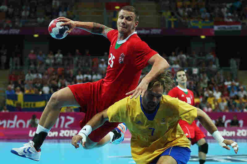 Szabolcs Zubai of Hungary shoots over Magnus Jernemyr of Sweden during the men's handball semifinal.