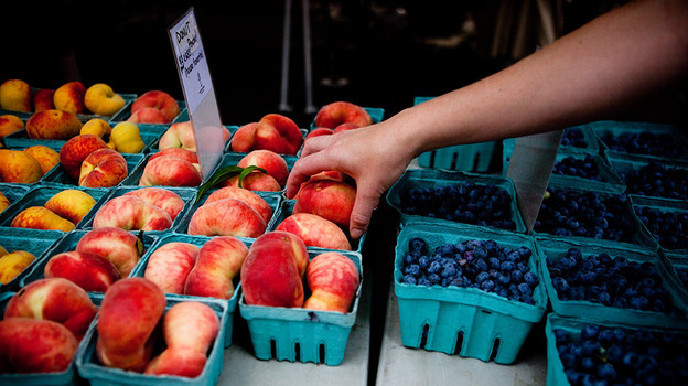 Shopper reaches for donut peaches at the Penn Quarter farmers' market in Washington, D.C. (NPR)