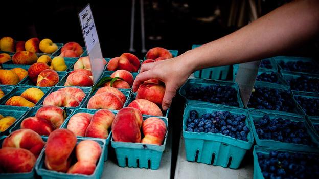 Shopper reaches for donut peaches at the Penn Quarter farmers' market in Washington, D.C. (NPR)
