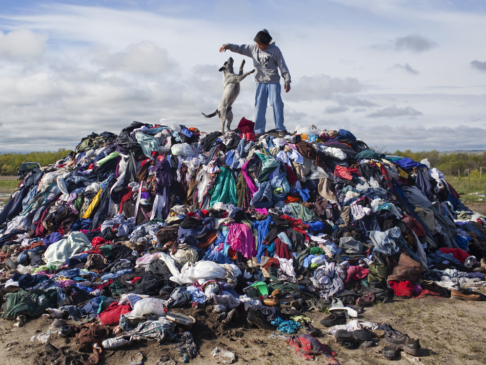 Mitchell Crow plays with his dog on what remains of 28,000 pounds of donated used clothes near Loneman, S.D. Unclaimed, the rain-soaked handouts began to go moldy during the summer.
