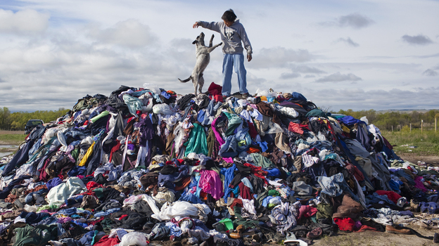 Mitchell Crow plays with his dog on what remains of 28,000 pounds of donated used clothes near Loneman, S.D. Unclaimed, the rain-soaked handouts began to go moldy during the summer. (National Geographic)