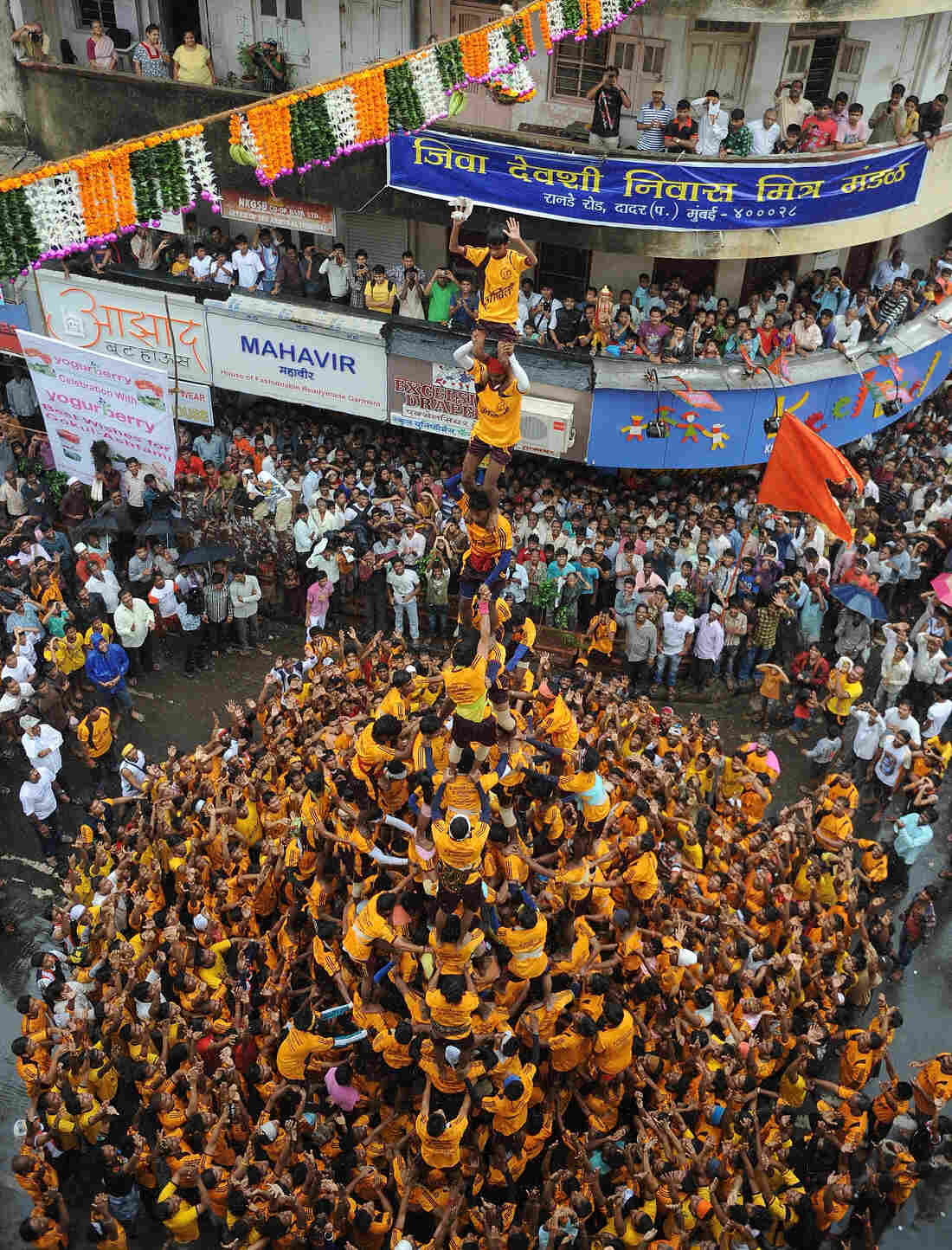 Almost to the top: Men and boys built this human pyramid in Mumbai as part of today's Janmashtami celebration. Their goal — a clay pot — is suspended over the street.