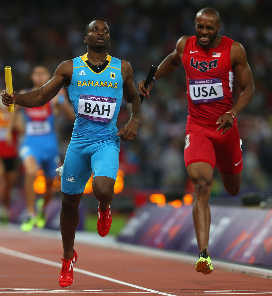 Ramon Miller (left) of the Bahamas crosses the finish line ahead of Team USA's Angelo Taylor to win the 4x400m relay gold medal at the London 2012 Olympics.