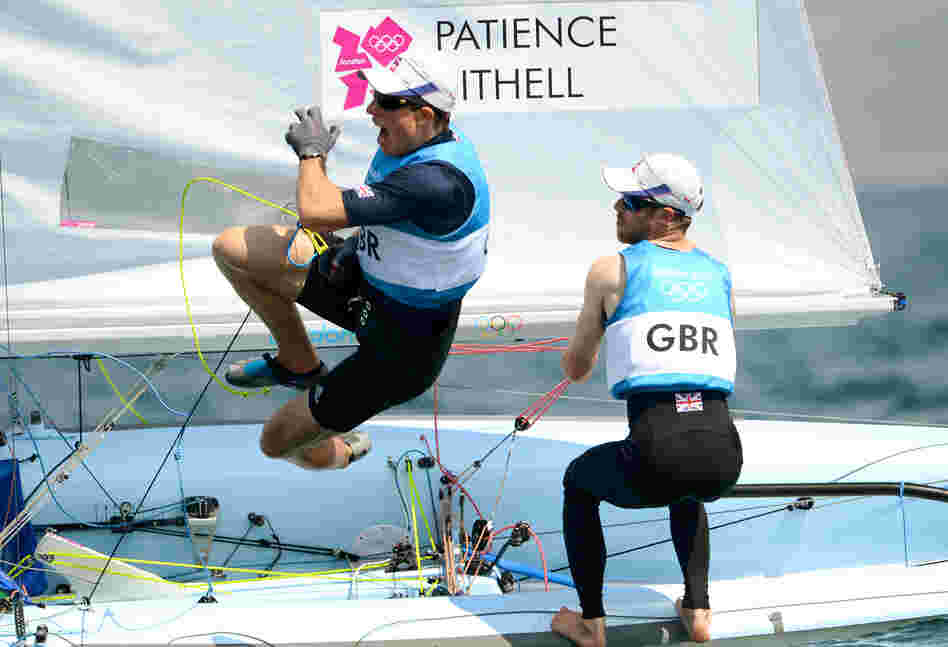 Great Britain's Stuart Bithell leaps off the boat while teammate Luke Patience sails on as they win silver in the men's sailing 470 two-person dinghy medal race in Weymouth, England.