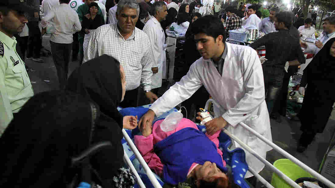 A medic attends to an injured woman as people gather outside a hospital in Ahar, Iran, after a strong earthquake hit northwestern part of the country Saturday.