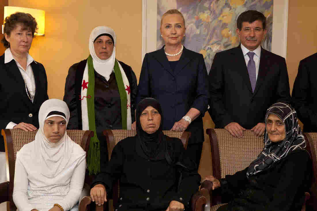 Turkey's Foreign Minister Ahmet Davutoglu (top right) and U.S. Secretary of State Hillary Clinton pose for a photograph with Syrian refugees in Turkey on Saturday.