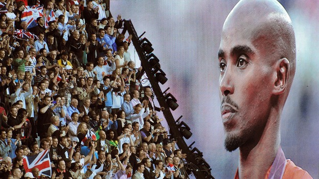 British runner Mo Farah is cheered as he appears on a giant screen at Olympic Stadium, accepting his gold medal for the 10,000 meters. Farah has become a celebrity in Britain since his win. (Getty Images)