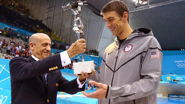 Michael Phelps accepts a trophy commemorating his status as the most-decorated Olympian from FINA president Julio Maglione. Phelps is retiring from Olympic swimming at 27.