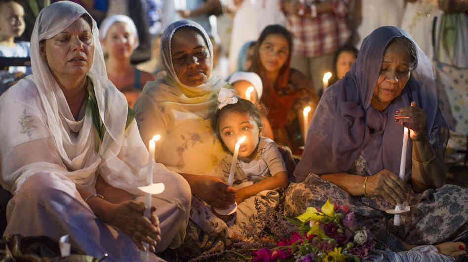 People attend a candlelight vigil for the victims of the Aug. 5 shooting at the Sikh Temple of Wisconsin in Oak Creek, Wis., on Aug. 7.