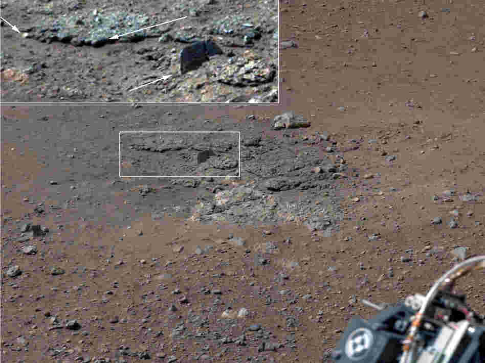 With the loose debris blasted away by the rockets, details of the underlying materials are clearly seen. Shown in the inset in the figure are pebbles up to 1.25 inches across (upper two arrows) and a larger clast 4 inches long protruding up by about 2 inches  from the layer in which it is embedded.
