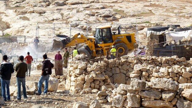 Israeli army tractors demolish a Palestinian home on Nov. 24, 2011, in the village of Yatta near Hebr
