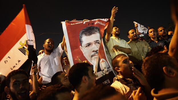 In Cairo Sunday night, thousands of Egyptians shouted political slogans in support of President Mohamed Morsi. (AFP/Getty Images)