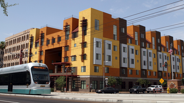 "A Metro Light Rail train rolls by the Devine Legacy apartment building along Central Avenue in Phoenix. The energy-efficient complex includes 65 ""urban style"" apartments. (Courtesy of Mica Thomas Mulloy)"