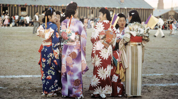 Young women wearing kimonos chat during an Obon celebration honoring ancestors at the Heart Mountain Relocation Center in Wyoming. ( Courtesy of Takao Bill Manbo/University of North Carolina Press)