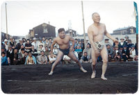 Sumo wrestlers share a light moment during a match in front of spectators.