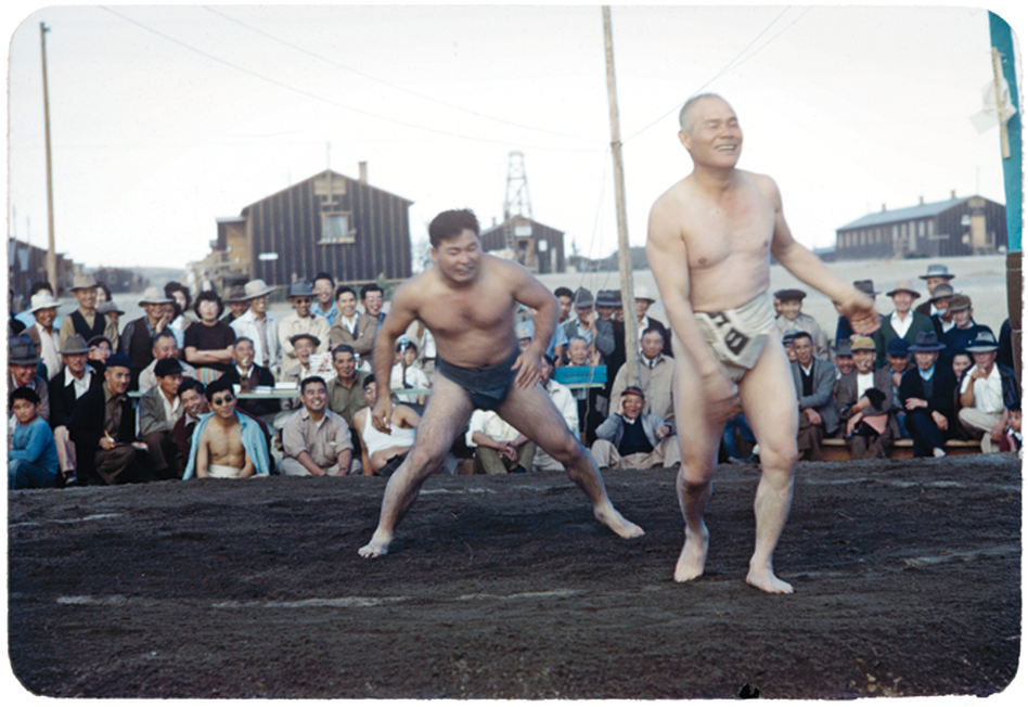 Sumo wrestlers share a light moment during a match in front of spectators. ( Courtesy of Takao Bill Manbo/University of North Carolina Press/Center for Documentary Studies, Duke University)
