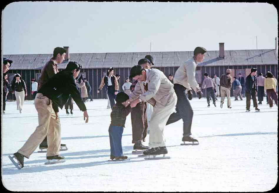 Photographer Bill Manbo's son Billy (center) gets a lesson in ice skating. Internees at Heart Mountain used fire hoses to create skating rinks around the camp during winter months.