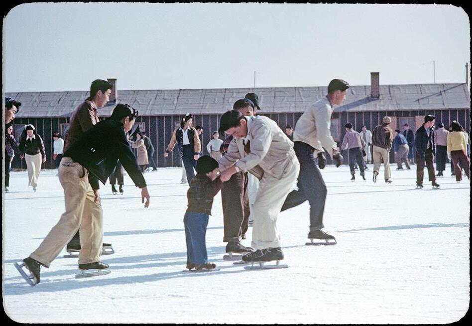 Photographer Bill Manbo's son Billy (center) gets a lesson in ice skating. Internees at Heart Mountain used fire hoses to create skating rinks around the camp during winter months. (Courtesy of Takao Bill Manbo/University of North Carolina Press/Center for Documentary Studies, Duke )