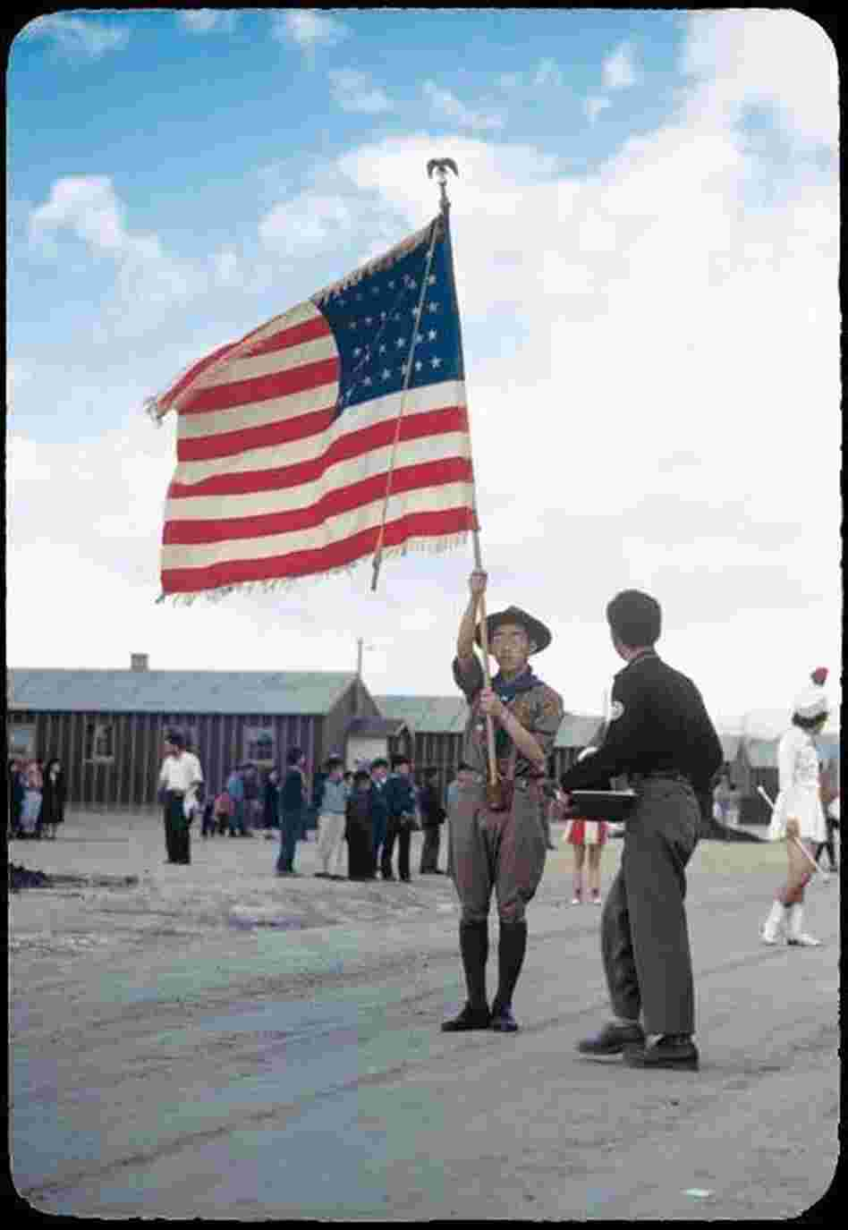 A Boy Scout carrying an American flag leads a parade through the Heart Mountain camp.