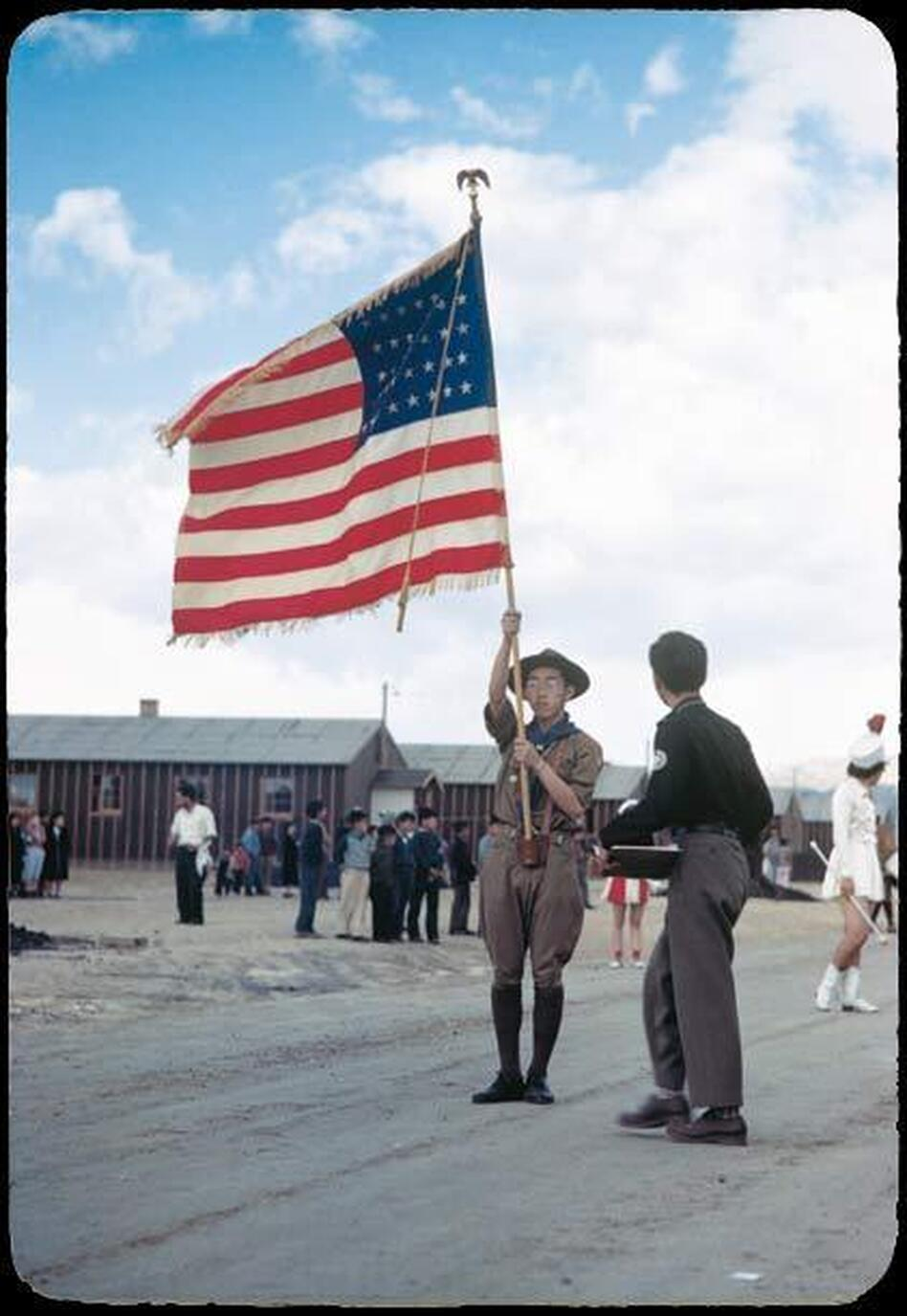 A Boy Scout carrying an American flag leads a parade through the Heart Mountain camp. (Courtesy of Takao Bill Manbo/University of North Carolina Press/Center for Documentary Studies, Duke University)
