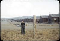 Billy Manbo clings to a barbed-wire fence enclosing a row of tar paper barracks.