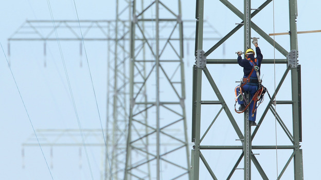 A worker on a newly constructed transmission tower near Buetzow, Germany, earlier this month. The German government plans to shut down nuclear power plants and is seeking to replace that production with power from renewable energy sources, especially wind turbines and solar parks. New power transmission lines will be needed. (Getty Images)