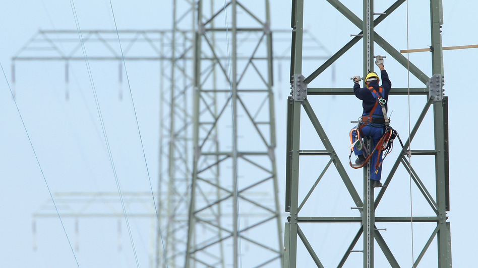 A worker on a newly constructed transmission tower near Buetzow, Germany, earlier this month. The German government plans to shut down nuclear power plants and is seeking to replace that production with power from renewable energy sources, especially wind turbines and solar parks. New power transmission lines will be needed.