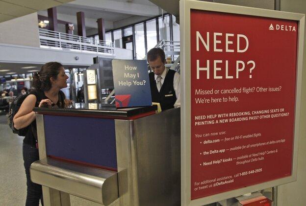 A Delta Airlines agent assists a woman at JFK Interna
