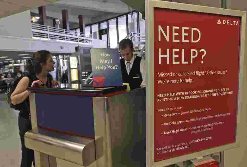 A Delta Airlines agent assists a woman at JFK International Airport in New York.