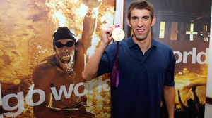 Michael Phelps poses with one of his record 22 Olympic medals after a press conference presented by Visa in London. Now that he's retired, Phelps hopes to see some of the world's cities that he's competed in.