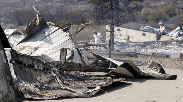 As embers still smolder, family members sift through the remains of their home that was destroyed in a wildfire. (AP)