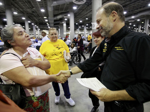 Sara Millan (left) thanks Neighborhood Assistance Corporation of America CEO Bruce Marks after NACA was able to reduce her family's mortgage during an event in Los Angeles in September 2010.