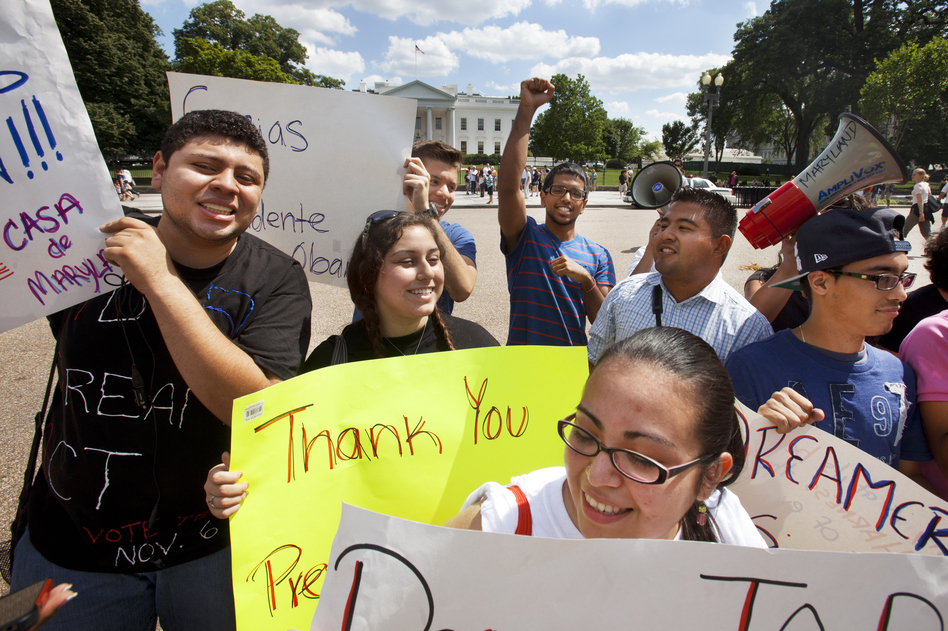"Ricky Campos, 23, and Katye Hernandez, 22, both illegal immigrants from El Salvador who live in Silver Spring, Md., hold signs saying ""Thank You President Obama"" after he announced the new policy in June."