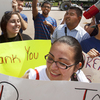 """Ricky Campos, 23, and Katye Hernandez, 22, both illegal immigrants from El Salvador who live in Silver Spring, Md., hold signs saying """"Thank You President Obama"""" after he announced the new policy in June."""