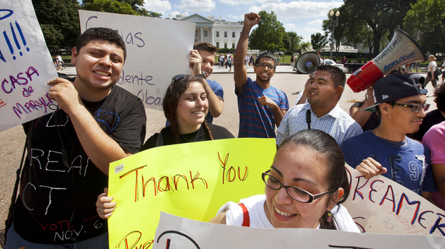 "Ricky Campos, 23, and Katye Hernandez, 22, both illegal immigrants from El Salvador who live in Silver Spring, Md., hold signs saying ""Thank You President Obama"" after he announced the new policy in June. (AP)"