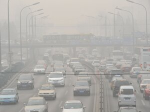 Vehicles make their way along a road on a smoggy day in Beijing on January 18, 2011. Beijing's government bowed to a vocal online campaign for a change in the way air quality is measured in the Chinese capital, one of the world's most polluted cities.