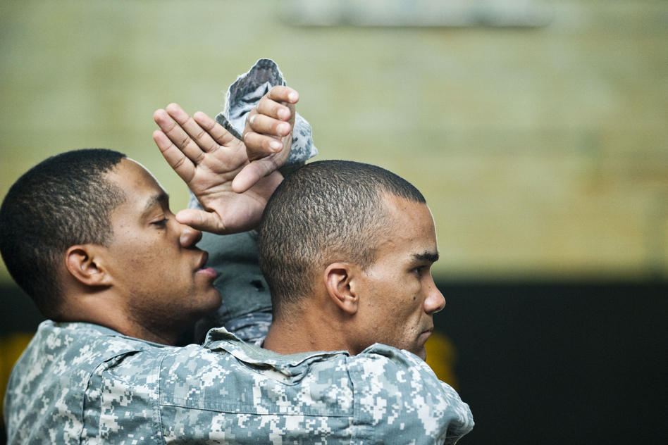 Sgt. 1st Class Isaac Cunningham (left) and Staff Sgt. Robert Terry practice maneuvers. (Pouya Dinat for NPR)