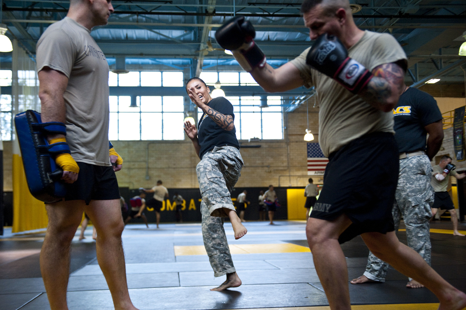U.S. Army combatives instructor Sgt. Teddra Rodriguez (center) demonstrates a move to two students. (Pouya Dinat for NPR)