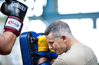 Maj. Christopher Carpenter takes a series of kicks and punches from a sparring partner. The soldiers take turns holding pads and practicing kicking and punching combos that will help them in close combat situations.