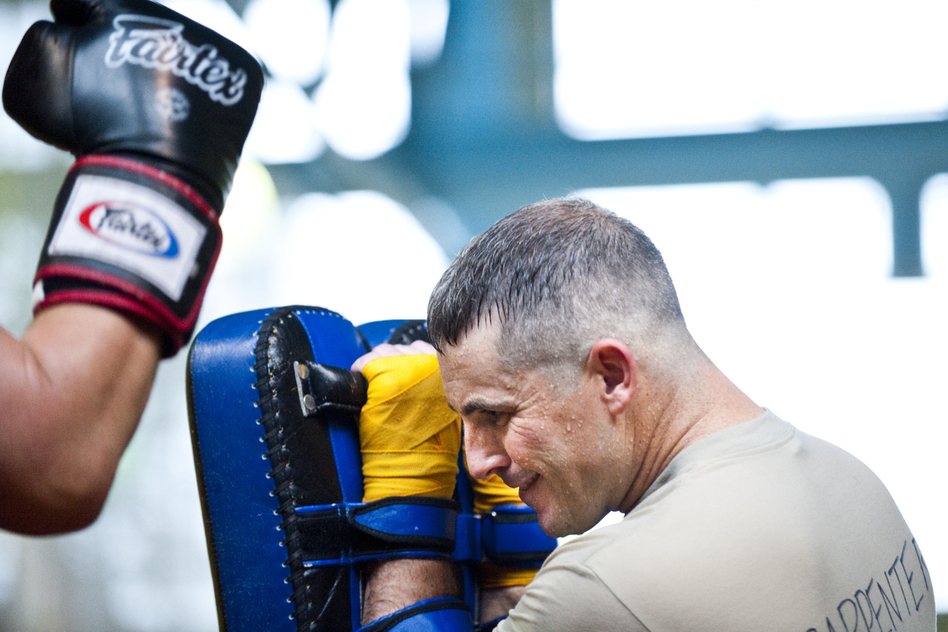 Maj. Christopher Carpenter takes a series of kicks and punches from a sparring partner. The soldiers take turns holding pads and practicing kicking and punching combos that will help them in close combat situations. (Pouya Dinat for NPR)