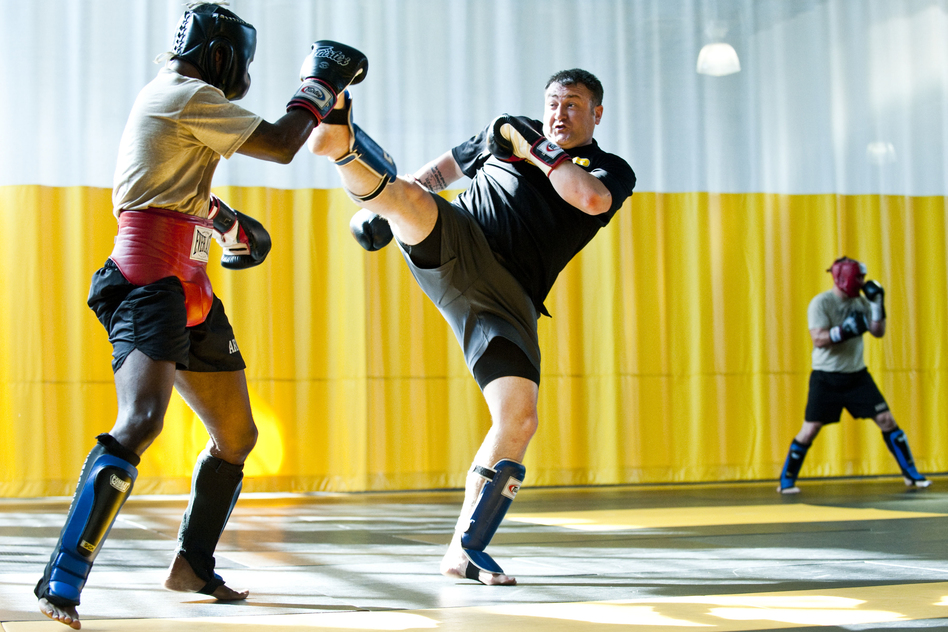 Sgt. 1st Class Kevin Rice, a master trainer at the U.S. Army Combatives School, drives back his partner with a high kick during a sparring session. (Pouya Dinat for NPR)