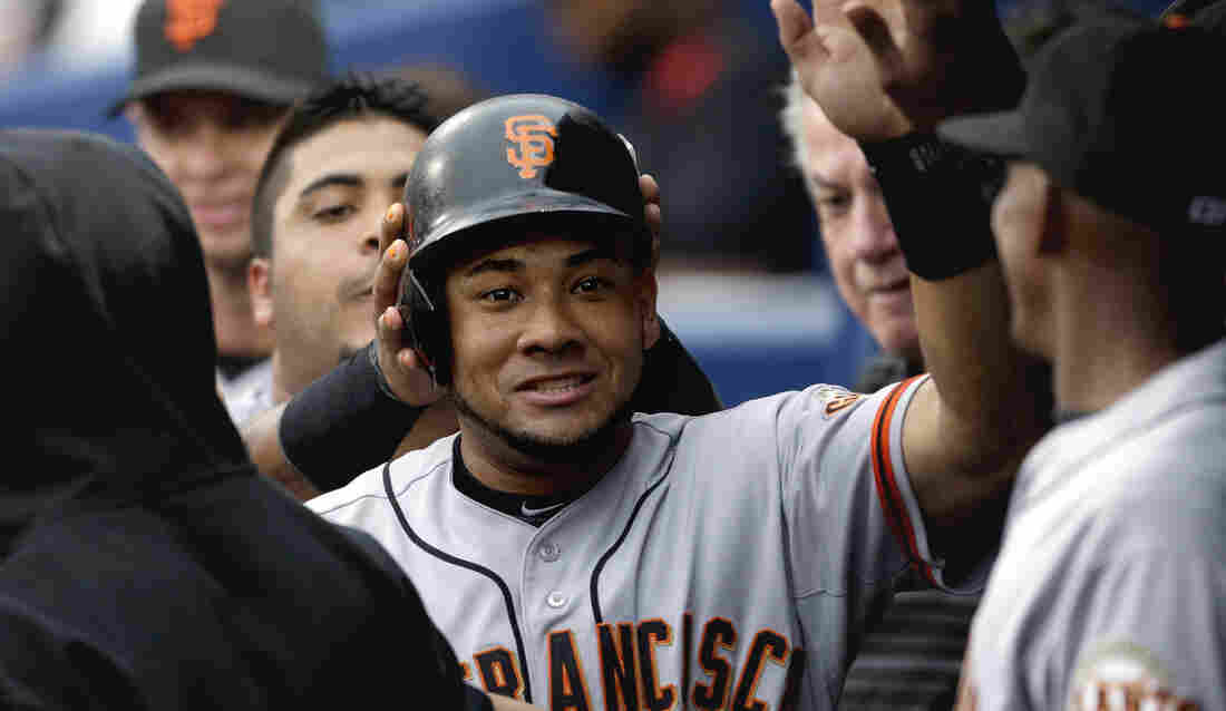San Francisco Giants' Melky Cabrera high-fives teammates after scoring off a single by teammate Buster Posey in the third inning of a baseball game against the Atlanta Braves in July.