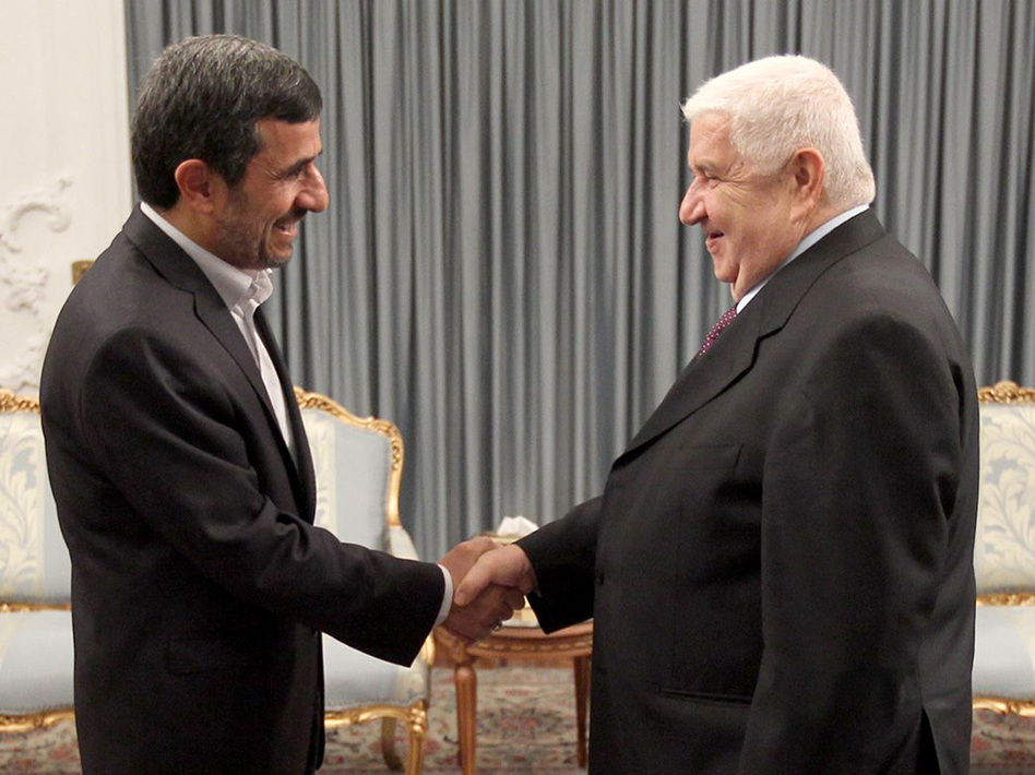 Iranian President Mahmoud Ahmadinejad (left) greets Syrian Foreign Minister Walid al-Muallem in the presidential palace in Tehran on July 29, in this official handout photo. The war in Syria threatens Iran's only ally in the Arab world. (UPI /Landov)