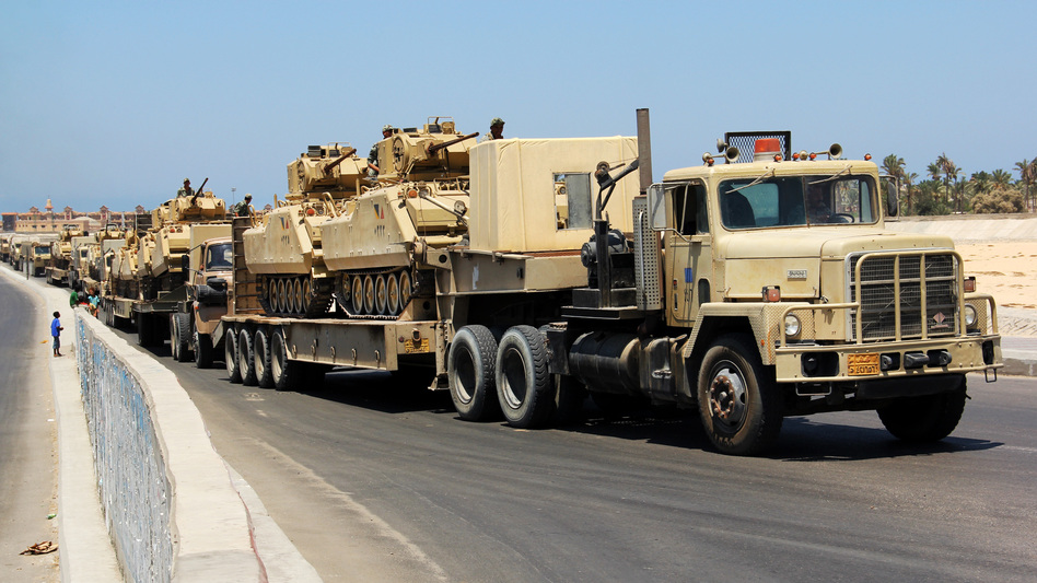 Army trucks carry Egyptian military tanks in El Arish, in the northern Sinai Peninsula, on Aug. 9. Security forces are conducting a major security campaign in the area after a deadly attack by masked gunmen on a border post left 16 soldiers dead.