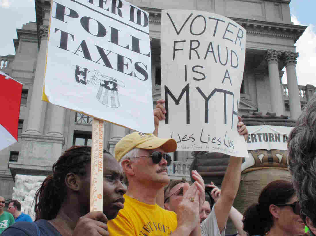 Demonstrators hold signs at an NAACP-organized rally on the steps of the Pennsylvania Capitol to protest the state's new voter identification law on July 24 in Harrisburg, Pa.